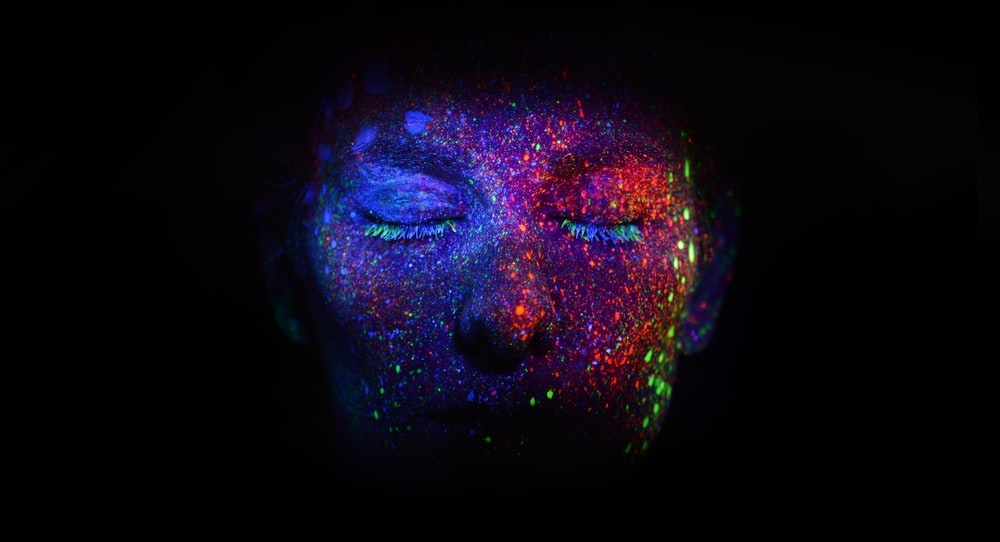 a face with closed eyes and neon paint spatters
