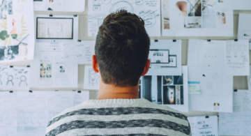 A man facing a wall full of notes