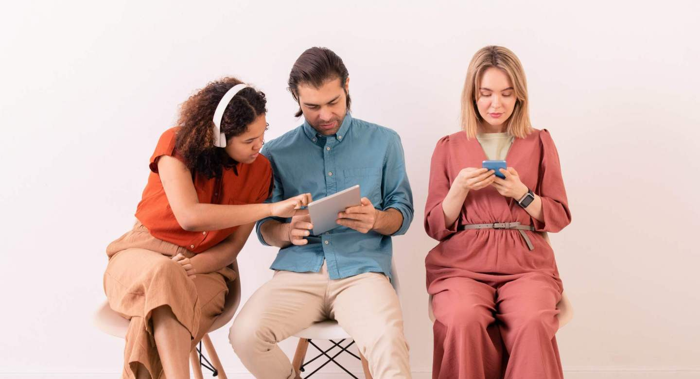 Brown-haired man sharing information on internet with Afro-American woman in wireless headphones while blonde girl texting sms